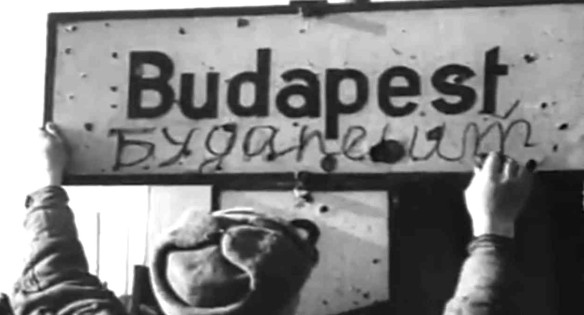 A Soviet soldier hangs a sign in Budapest with the city's name translated into Russian