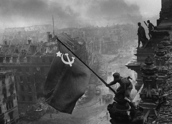 The Soviet flag being placed over the Reichstag in Berlin - the ultimate sign of Soviet victory and German defeat (Credit: Yevgeny Khaldei)