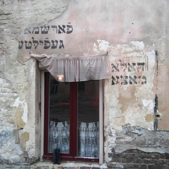 Hebrew inscriptions from the Golden Rose synagogue above and beside doors to the At The Golden Rose Restaurant