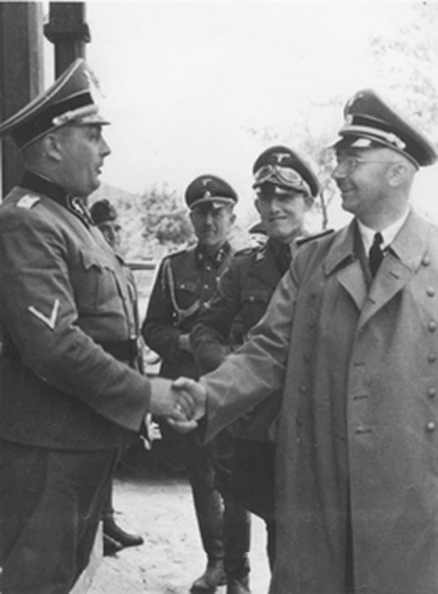 Fritz Katzmann stands to the left of Reichsfuehrer SS Heinrich Himmler during an official visit to the Janowska concentration camp in Lwow