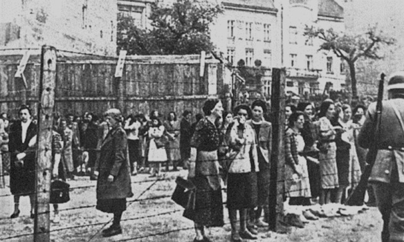 Jewish women stand at the fence of the Lwow Ghetto in the spring of 1942