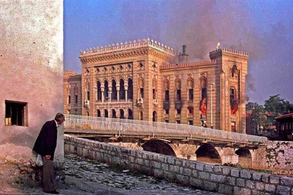 A man watches the Bosnian National & University Library on fire in August 1992