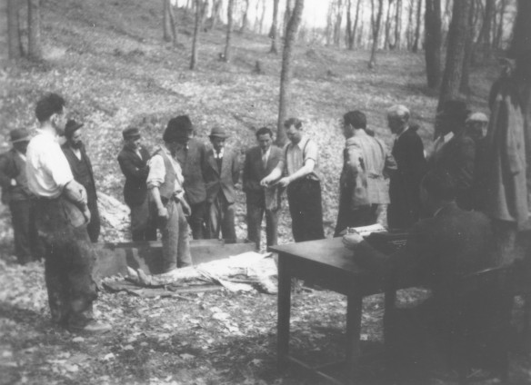 The Horror - Romanian workmen examine an exhumed body of a Jew killed in the ghetto in Dej